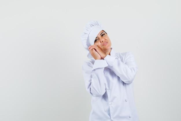Vrouwelijke chef-kok die op gevouwen handen als hoofdkussen in wit uniform leunt