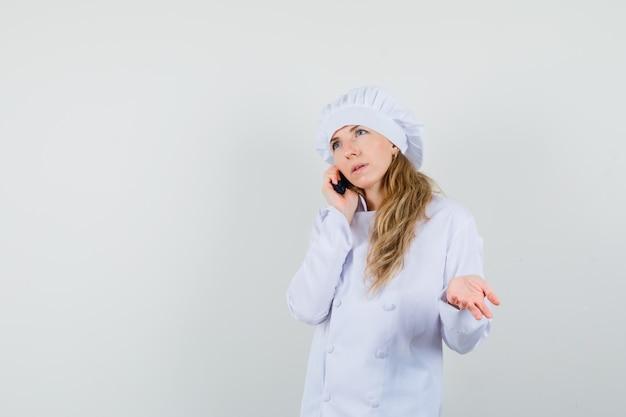 Vrouwelijke chef-kok die op mobiele telefoon in wit uniform spreekt en verward kijkt.