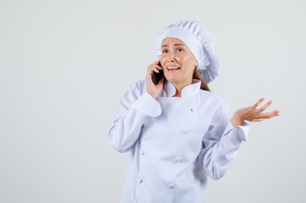 Vrouwelijke chef-kok die op mobiele telefoon in wit uniform spreekt en vrolijk kijkt. vooraanzicht.