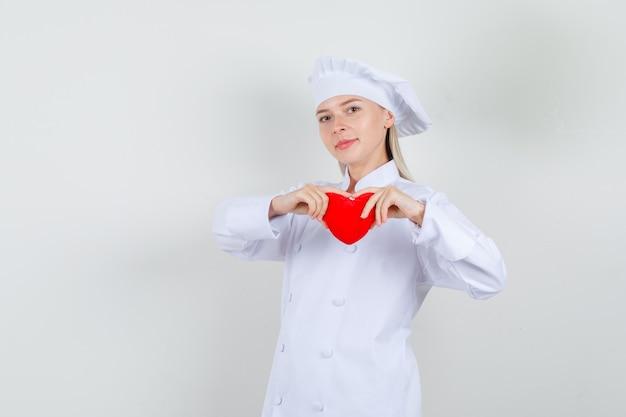 Vrouwelijke chef-kok die rood hart houdt en in wit uniform glimlacht