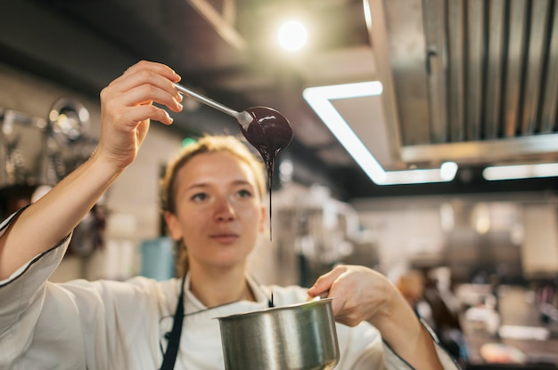 Vrouwelijke chef-kok die saus controleert