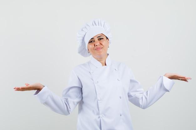 Vrouwelijke chef-kok die schalengebaar in wit uniform toont en verward kijkt.