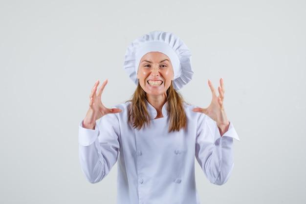 Vrouwelijke chef-kok die tanden op elkaar klemt en handen met woede opheft in wit uniform vooraanzicht.