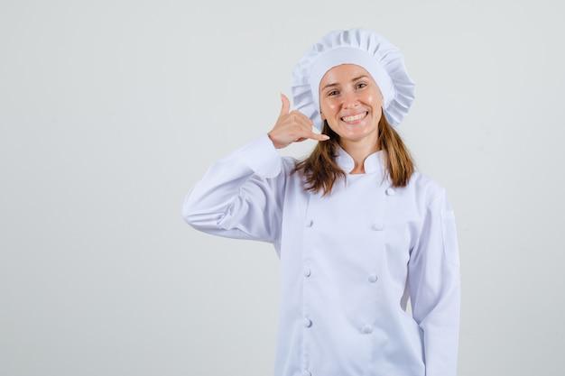 Vrouwelijke chef-kok die telefoongebaar in wit uniform toont en blij kijkt. vooraanzicht.