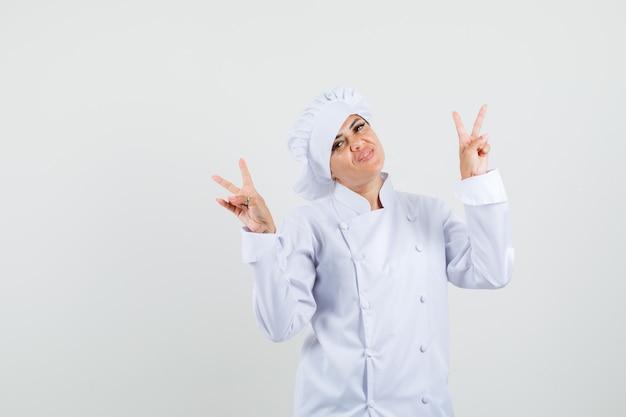 Vrouwelijke chef-kok die v-teken in wit uniform toont en vrolijk kijkt.