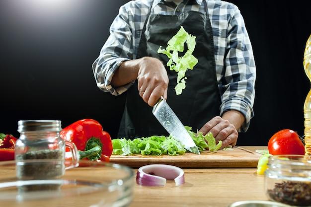 Vrouwelijke chef-kok die verse groenten snijdt