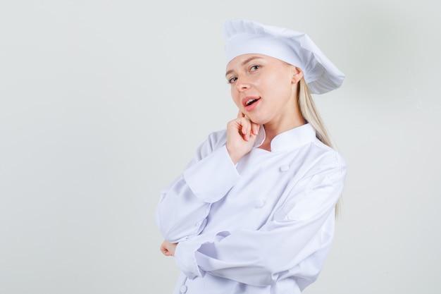 Vrouwelijke chef-kok die vinger op wang in wit uniform houdt en charmant kijkt.