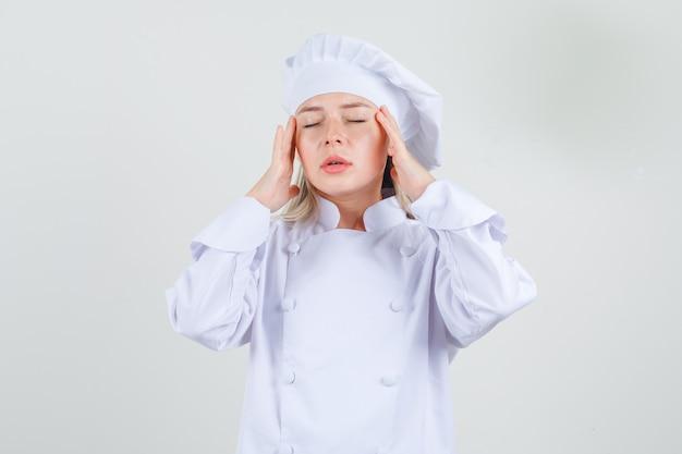 Vrouwelijke chef-kok die vingers op tempels in wit uniform houdt en moe kijkt