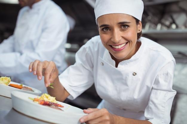 Vrouwelijke chef-kok die voedsel in keuken bij restaurant versieren