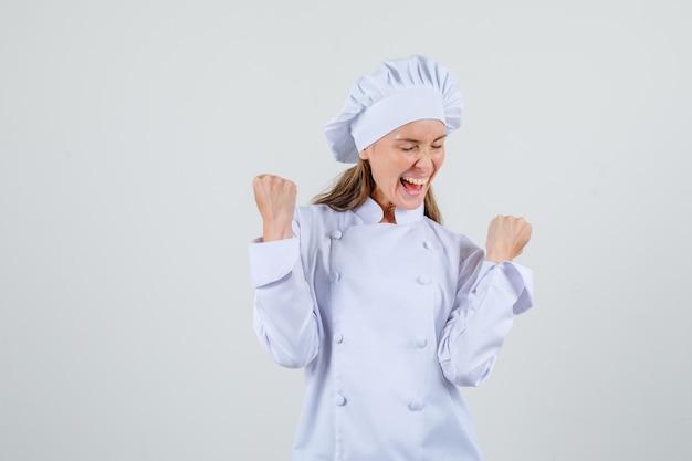 Vrouwelijke chef-kok die winnaargebaar in wit uniform toont en gelukkig kijkt. vooraanzicht.