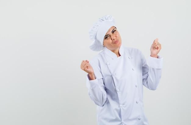 Vrouwelijke chef-kok die winnaargebaar in wit uniform toont en gelukkig kijkt