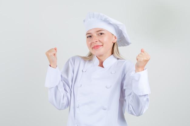 Vrouwelijke chef-kok die winnaargebaar toont en in wit uniform glimlacht