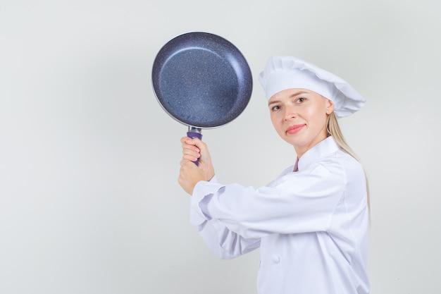 Vrouwelijke chef-kok dreigt met koekenpan in wit uniform en ziet er grappig uit