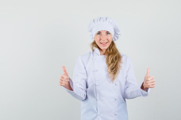 Vrouwelijke chef-kok dubbele duimen opdagen in wit uniform en gelukkig kijken