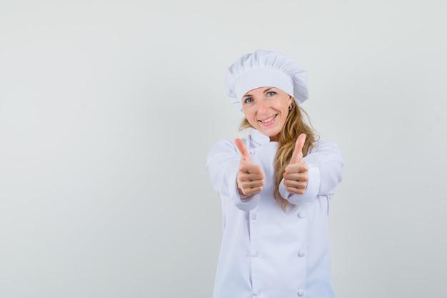 Vrouwelijke chef-kok dubbele duimen opdagen in wit uniform en vrolijk kijken