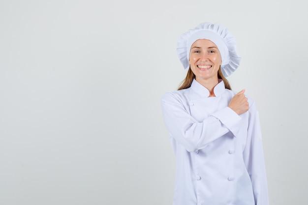 Vrouwelijke chef-kok gebaren met gebalde vuist in wit uniform en vrolijk kijken