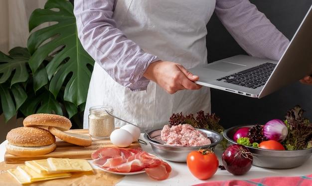 Vrouwelijke chef-kok grote hamburger of cheeseburger koken en laptop gebruiken met kookrecept tutorial.