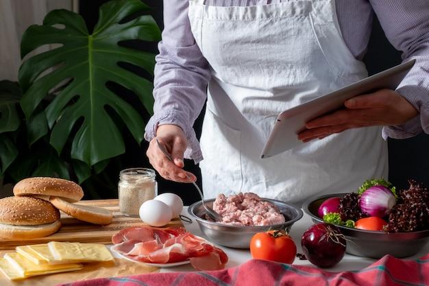 Vrouwelijke chef-kok grote hamburger of cheeseburger koken en tablet gebruiken met kookrecept tutorial.