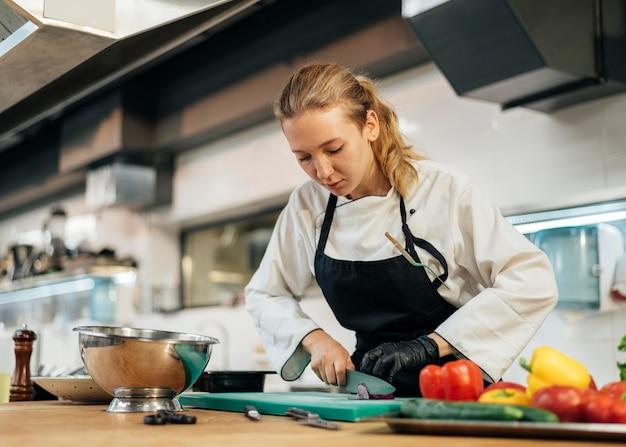Vrouwelijke chef-kok hakken groenten in de keuken