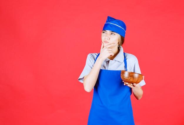 Vrouwelijke chef-kok in blauwe schort die een chinese koperen noedelkop vasthoudt en denkt
