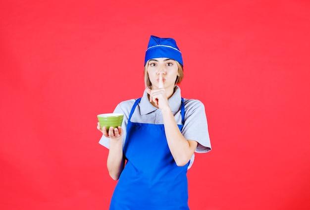 Vrouwelijke chef-kok in blauwe schort die een groene noedelbeker vasthoudt en om stilte vraagt