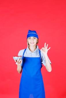 Vrouwelijke chef-kok in blauwe schort die een noedelkop houdt en het teken van de tevredenheidshand toont