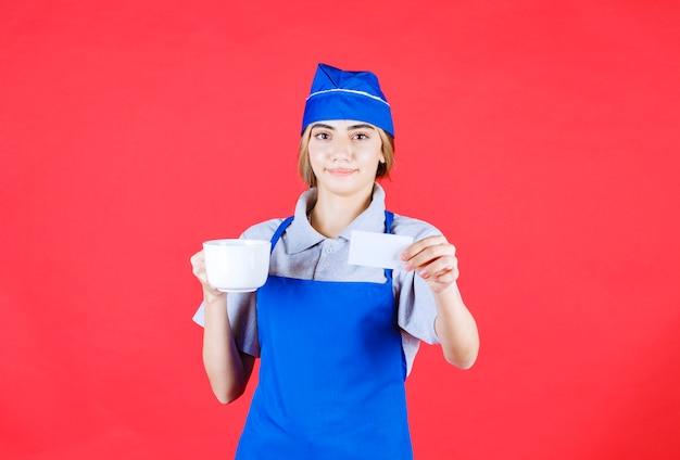 Vrouwelijke chef-kok in blauwe schort die een witte keramische noedelbeker vasthoudt en haar visitekaartje presenteert
