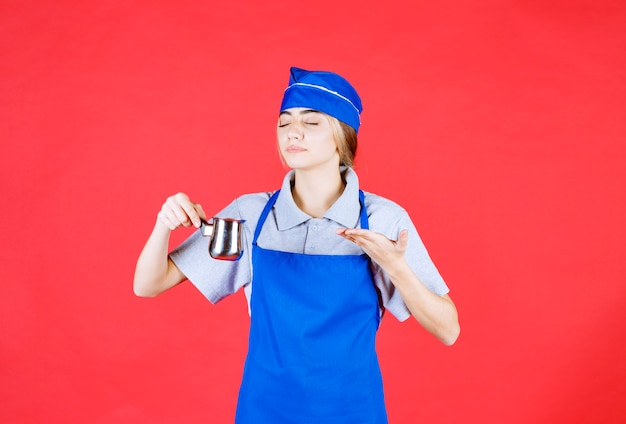 Vrouwelijke chef-kok in blauwe schort die een zilveren turkse handmatige koffiepot vasthoudt en de smaak ruikt
