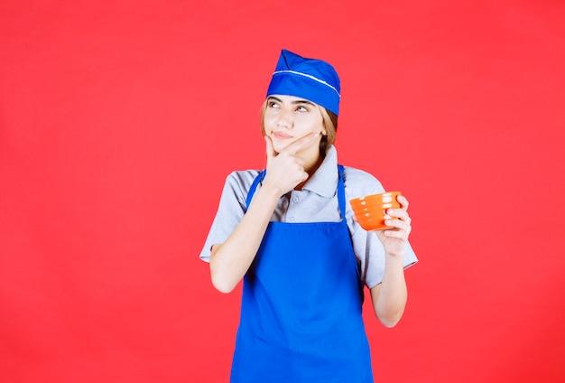 Vrouwelijke chef-kok in blauwe schort met een noedelbeker en kijkt verward en denkt na over hoe ze het lekkerder kan maken