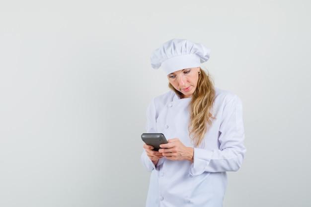 Vrouwelijke chef-kok in wit uniform berekeningen maken op de rekenmachine