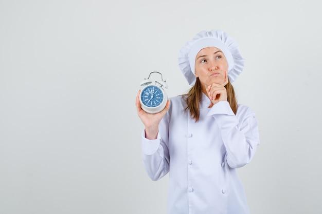 Vrouwelijke chef-kok in wit uniform denken terwijl wekker vasthoudt en hoopvol kijkt