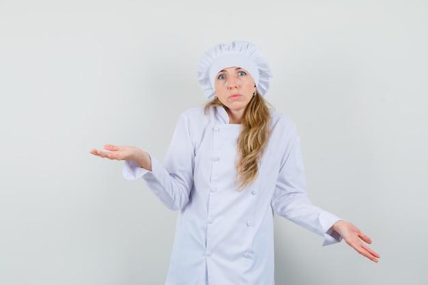 Vrouwelijke chef-kok in wit uniform die hulpeloos gebaar toont door verward op te halen en te kijken
