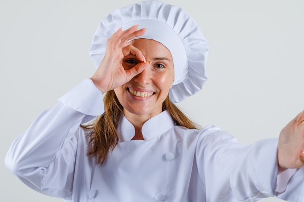 Vrouwelijke chef-kok in wit uniform doet ok teken op oog en kijkt vrolijk