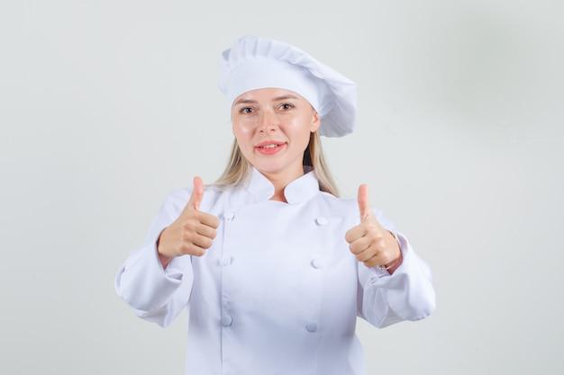 Vrouwelijke chef-kok in wit uniform duimen opdagen en positief kijken