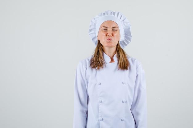 Vrouwelijke chef-kok in wit uniform fronst haar gezicht en kijkt geïrriteerd