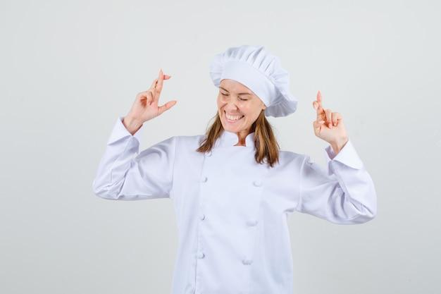 Vrouwelijke chef-kok in wit uniform gekruiste vingers vasthouden en op zoek gelukkig