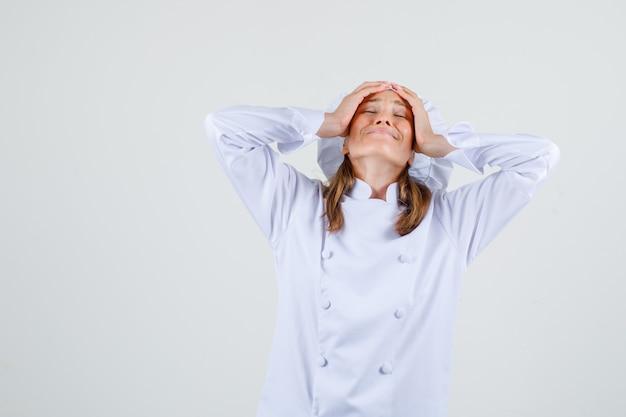 Vrouwelijke chef-kok in wit uniform hand in hand op het hoofd en uitgeput op zoek