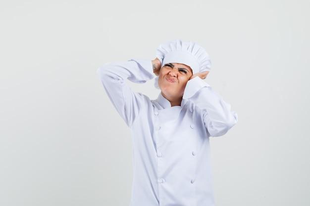 Vrouwelijke chef-kok in wit uniform hand in hand op oren en op zoek geïrriteerd