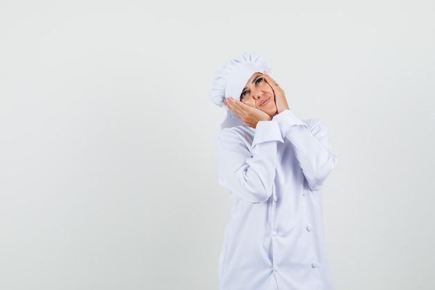 Vrouwelijke chef-kok in wit uniform hand in hand op wangen en schattig op zoek
