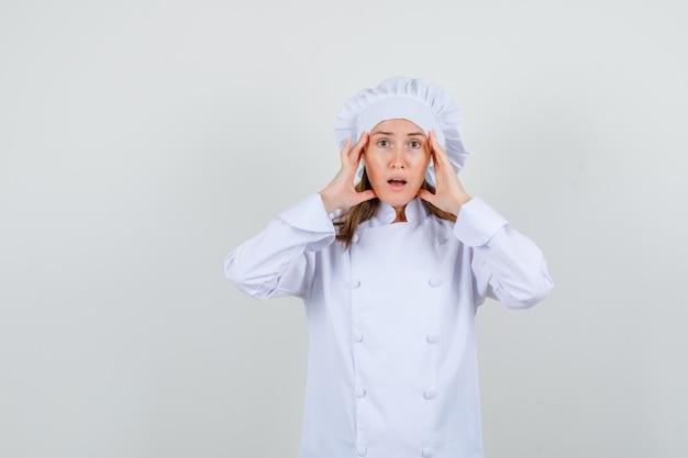 Vrouwelijke chef-kok in wit uniform hoofd met handen te houden en uitgeput te kijken