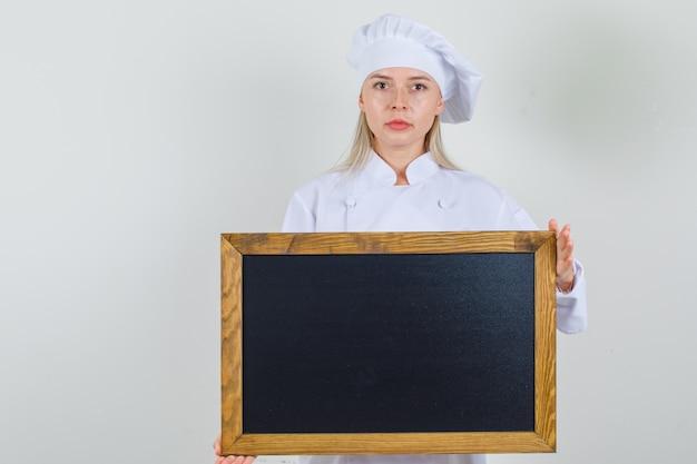 Vrouwelijke chef-kok in wit uniform houden bord en serieus kijken