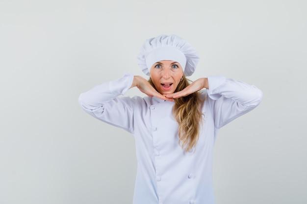 Vrouwelijke chef-kok in wit uniform houden gezamenlijke handen onder de kin en ziet er schattig uit