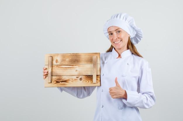 Vrouwelijke chef-kok in wit uniform houten dienblad met duim omhoog houden en vrolijk kijken