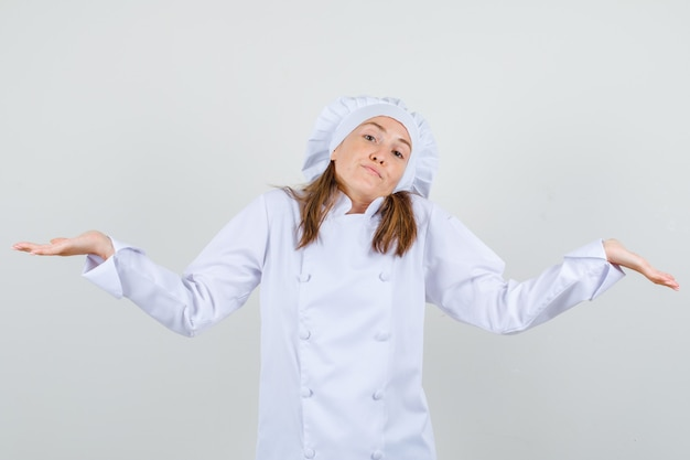 Vrouwelijke chef-kok in wit uniform hulpeloos gebaar tonen en verward kijken