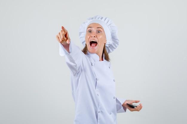 Vrouwelijke chef-kok in wit uniform iets laten zien terwijl hij smartphone vasthoudt