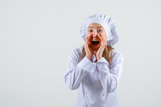 Vrouwelijke chef-kok in wit uniform iets vertrouwelijks vertellen en optimistisch kijken