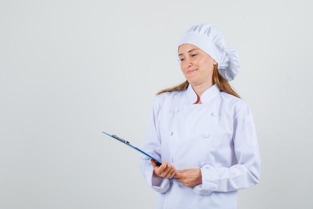 Vrouwelijke chef-kok in wit uniform klembord houden en glimlachen