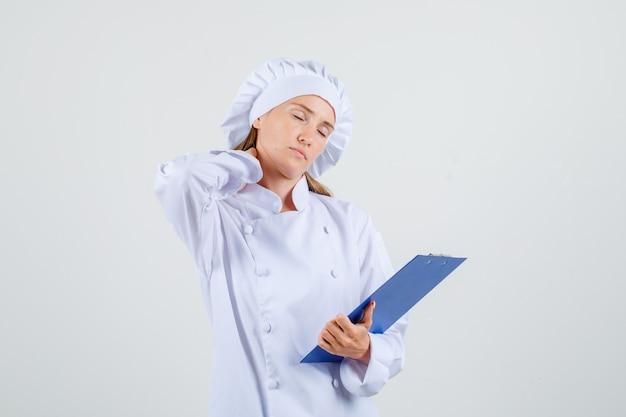 Vrouwelijke chef-kok in wit uniform klembord met hand op nek houden en moe kijken