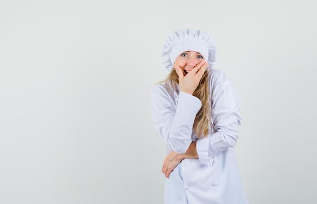 Vrouwelijke chef-kok in wit uniform lachen met hand op mond en gelukkig kijken