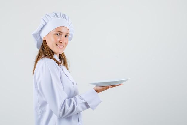 Vrouwelijke chef-kok in wit uniform leeg bord te houden en blij te kijken.